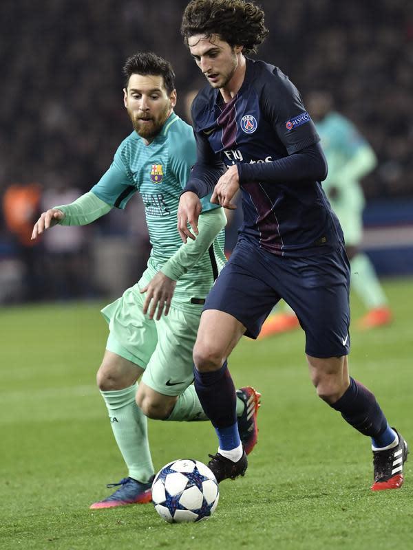 Gelandang PSG, Adrien Rabiot berusaha mengiring bola dari kejaran penyerang Barcelona, Lionel Messi pada pertandingan babak 16 besar Liga Champions di Parc Des Princes, Paris, (15/2). PSG menang 4-0 atas Barcelona. (AFP Photo / Philipe Lopez)
