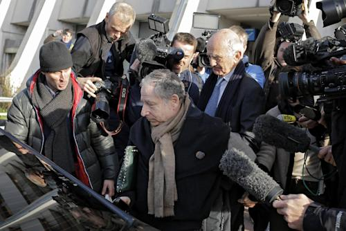 "President of the Federation Internationale de l'Automobile, F.I.A., Jean Todt, center, and Professor Gerard Saillant, behind him, leave the Grenoble hospital, French Alps, where former seven-time Formula One champion Michael Schumacher is being treated after sustaining a head injury during a ski accident, Tuesday, Dec. 31, 2013. Michael Schumacher underwent a second surgery after a brain scan showed small, ""surprising"" signs of improvement, but grim doctors said Tuesday they could offer no insight into the prognosis for the Formula 1 champion. (AP Photo/Laurent Cipriani)"