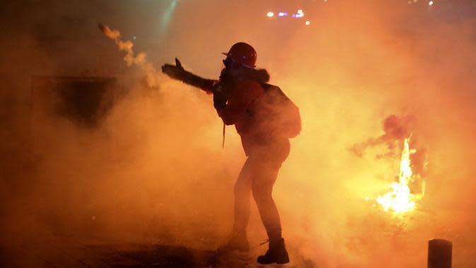 Demonstran antipemerintah melemparkan kembali tabung gas air mata kepada polisi antihuru-hara saat protes menentang elite penguasa di Beirut, Lebanon, Selasa (14/1/2020). Demonstran menganggap elite penguasa gagal mengatasi ekonomi yang menurun tajam. (AP Photo/Hussein Malla)