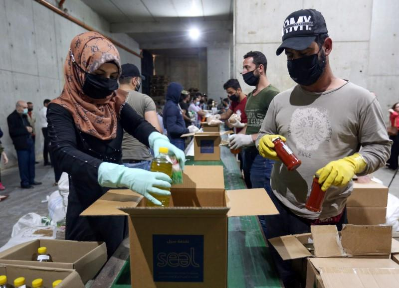 Volunteers wearing protective masks and gloves fill boxes with food for distribution to people in need, in Beirut