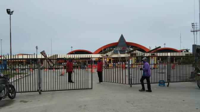 Petugas Bandara Sentani di Kabupaten Jayapura menutup pintu masuk dan keluar bandara. Hal ini diberlakukan hingga 14 hari kedepan untuk penghentian sementara penerbangan penumpang. (Liputan6.com/Katharina Janur/Findi)