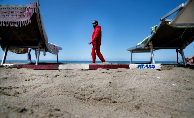 A lifeguard wearing a protective facemask checks the distance between sun beds at Fregene beach near Rome