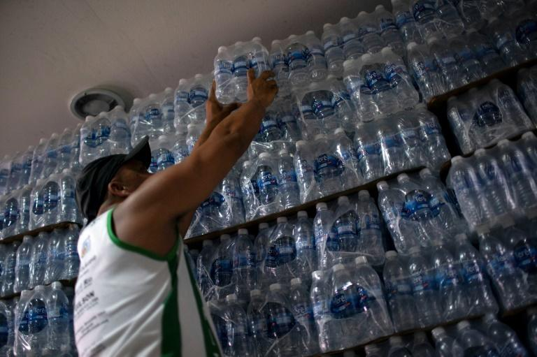 In this file photo taken on January 15, 2020, a man buys bottled water at a liquor store in the Lapa neighborhood of Rio de Janeiro