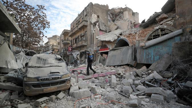 Warga berjalan melewati puing-puing bangunan setelah serangan udara rezim di Kota Ariha, Idlib, Suriah, Rabu (15/1/2020). Pada 9 Januari, gencatan senjata di Idlib dideklarasikan dengan inisiatif Rusia dan Turki. (Omar HAJ KADOUR/AFP)