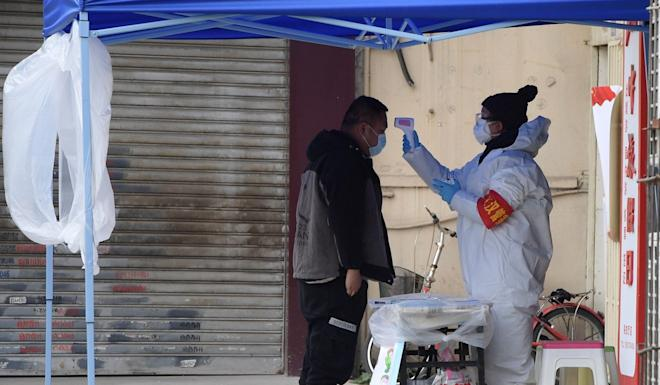 A community inspector measures a visitor's temperature at the entrance of a residential block in Wuhan, Hubei province, epicentre of the deadly coronavirus. Photo: Xinhua