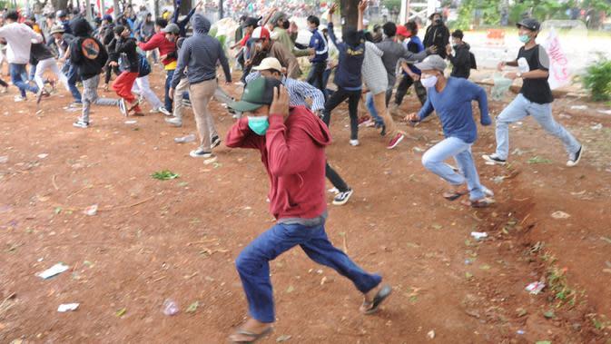 Sejumlah pengunjuk rasa melemparkan batu di Jalan MH Thamrin, Jakarta, Selas (13/10/2020). Massa pengunjuk rasa yang menolak Omnibus Law akhirnya dibubarkan dengan tembakan gas air mata. (merdeka.com/Arie Basuki)
