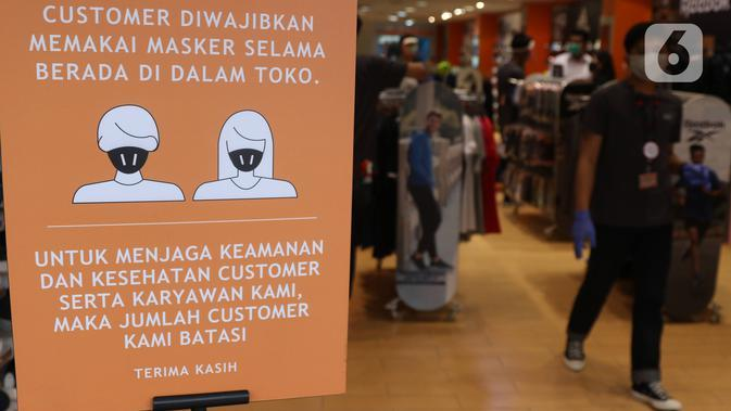 Papan bertuliskan aturan pemakaian masker dan pembatasan jarak kepada pengunjung di salah satu toko di Pasar Baru Jakarta Pusat, Selasa (9/6/2020). Pusat perbelanjaan tersebut kembali dibuka, meski masih dalam masa Pembatasan Sosial Berskala Besar (PSBB) transisi. (Liputan6.com/Angga Yuniar)