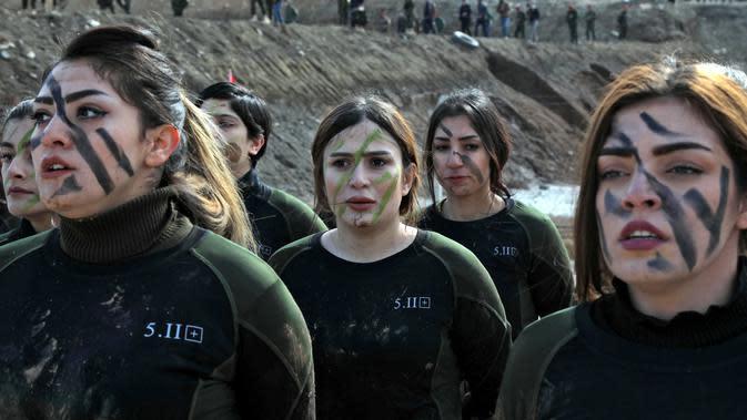 Pasukan perempuan Peshmerga berbaris saat berlatihan dalam upacara kelulusan di Kota Soran, Irak, Rabu (12/2/2020). Latihan militer pasukan bersenjata Kurdi tersebut dilakukan sekitar 100 kilometer timur laut ibu kota otonomi wilayah Kurdi di Irak, Arbil. (SAFIN HAMED/AFP)