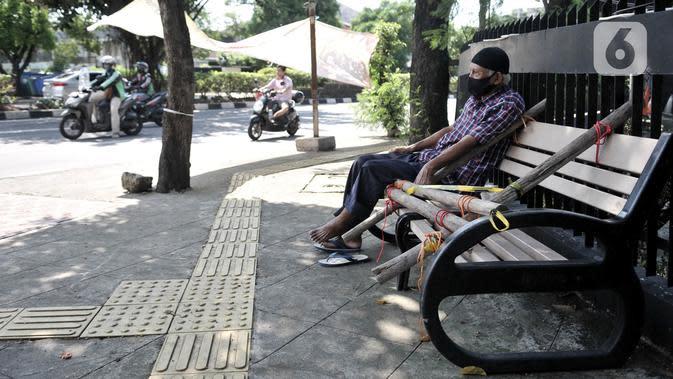 Warga nekat duduk di bangku trotoar yang disegel garis pembatas dan ditutupi bambu di kawasan Rawamangun, Jakarta, Minggu (3/5/2020). Bangku trotoar di sepanjang jalan Rawamangun disegel untuk mencegah kerumunan warga sebagai upaya memutus rantai penyebaran COVID-19. (merdeka.com/Iqbal S. Nugroho)
