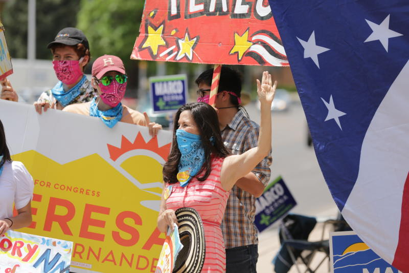 """Democratic congressional candidate Teresa Leger Fernandez, in the blue mask, cheers on supporters at a polling station Tuesday, June 2, 2020, in Santa Fe, N.M. Fernandez was flanked by her three sons, left to right, Alisandro, Dario and Abelino. The sign she holds, """"Ahora es cuando,"""" is Spanish for """"Now is the time."""" (AP Photo/Cedar Attanasio)"""