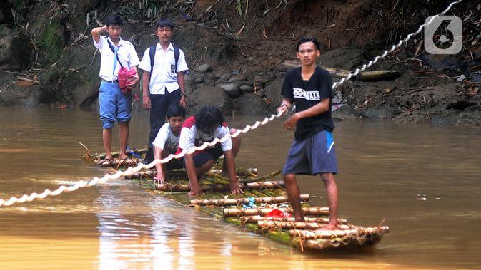 Sejumlah siswa menyeberangi Sungai Cikaniki dengan rakit di Rumpin, Bogor, Jawa Barat, Rabu (15/1/2020). Akibat banjir bandang merobohkan jembatan yang menghubungkan Desa Tonjong Rumpin dan Desa Kantalarang Leuwiliang, warga terpaksa memanfaatkan perahu rakit untuk melintas (merdeka.com/Arie Basuki)