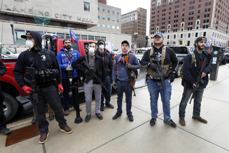 In this April 15, 2020 photo, protesters carry guns outside the Capitol Building in Lansing, Mich. Michigan Attorney General Dana Nessel said Friday, May 8, 2020, that a commission overseeing the state Capitol can legally ban guns from the building, contradicting panel leaders' contention that only the Legislature can do so. (AP Photo/Paul Sancya)