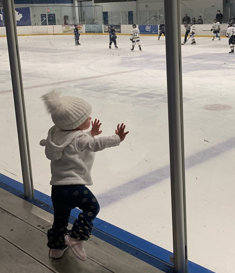 Chloe Wiegand standing at a hockey game in Indiana wearing a bobble hat and leaning on the glass. She died after she fell from a cruise ship window in Puerto Rico.
