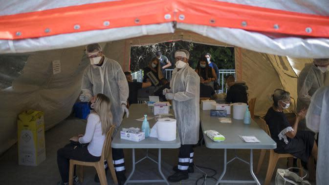Orang-orang menerima tes COVID-19 di pusat pengujian di Marseille, Prancis, 24 September 2020. Jumlah kematian akibat COVID-19 dunia setara dengan sekitar 226 orang meninggal per jam atau satu orang meninggal setiap 16 detik. (AP Photo/Daniel Cole, File)