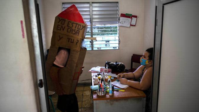 Pensiunan perawat, Feridia Rojas mengenakan kotak kardus untuk melindungi dirinya dari penyebaran Covid-19 mampir untuk kunjungan persahabatan dengan dokter keluarga, di Havana, Kuba, 8 Juli 2020. Kardus pelindung itu dilengkapi pesan yang ditulis tangan,