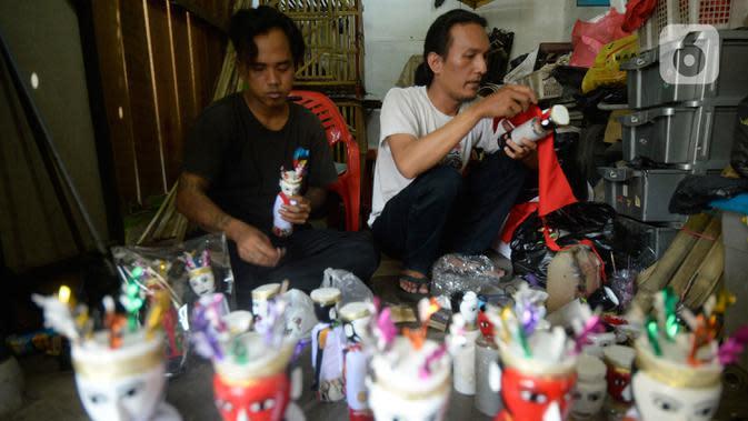 Pengrajin sedang menyelesaikan ondel-ondel hiasan yang terbuat dari limbah plastik botol di Kampung Sawah Lama, Ciputat, Tangerang Selatan, banten, Jumat (4/9/2020). Dalam satu hari perajin bisa menyelesaikan 30 biji kerajinan ondel-ondel budaya khas Betawi. (merdeka.com/Dwi Narwoko)