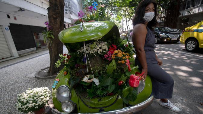 Roberta Machado dari Brasil berpose dengan Volkswagen Beetle 1969 miliknya yang diubah menjadi toko bunga keliling di Copacabana, Rio de Janeiro, Rabu (14/10/2020). Perempuan 51 tahun ini mengubah VW kodok untuk bertahan dari krisis akibat pandemi COVID-19. (MAURO PIMENTEL/AFP)