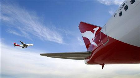 File photo of Qantas Boeing 747 flying past a 767 airplane with a newly unveiled Qantas logo on its tail in Sydney