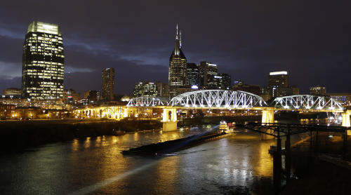 This Jan. 15, 2014 photo shows the Shelby Street pedestrian bridge spanning the Cumberland River in Nashville, Tenn. The banks of the Cumberland River in downtown Nashville are more than a place to watch barges pass. The bridge is one of the best viewpoints for the Nashville skyline that inspired Bob Dylan to write a country album. (AP Photo/Mark Humphrey)