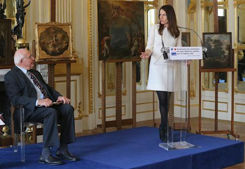 American Thomas Selldorff, left, listening to France's Culture Minister Aurelie Filippetti, right, during a ceremony at the Culture Ministry in Paris, France, Tuesday, March 19, 2013, to return seven paintings taken from their Jewish owners during World War II, as part of ongoing efforts to give back hundreds of looted artworks that still hang in the Louvre and other French museums. Selldorff reclaimed six German and Italian paintings that his grandfather, Richard Neumann, was forced to sell during World War II to flee Nazi occupation, and another painting was returned to other recipients. In the background are some of the returned paintings. Sign in front reads: Ceremony of return of seven paintings spoils from the Nazi regime.(AP Photo/Michel Euler)