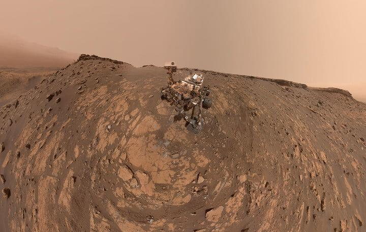 """This selfie was taken by NASA's Curiosity Mars rover on Feb. 26, 2020 (the 2,687th Martian day, or sol, of the mission). The crumbling rock layer at the top of the image is """"the Greenheugh Pediment,"""" which Curiosity climbed soon after taking the image."""