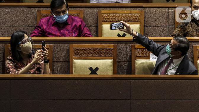 Menteri Keuangan Sri Mulyani (kiri) bersama Menteri Hukum dan HAM Yasonna Laoly (kanan) saat mengikuti Rapat Paripurna di Kompleks Parlemen, Jakarta (5/10/2020).Rapat membahas berbagai agenda, salah satunya mengesahkan RUU Omnibus Law Cipta Kerja menjadi UU. (Liputan6.com/JohanTallo)