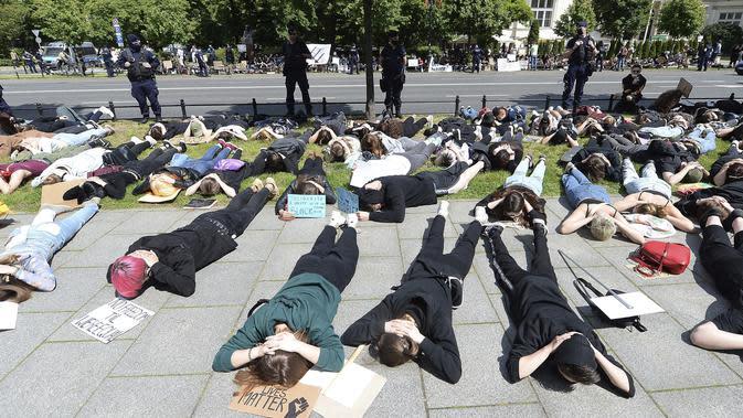 Aksi demonstran saat berunjuk rasa memprotes kematian George Floyd di depan Kedutaan Besar AS di Otwock, Polandia, Kamis (4/6/2020). Kematian pria kulit hitam George Floyd saat ditangkap oleh polisi Amerika Serikat memicu kemarahan di sejumlah negara. (AP Photo/Czarek Sokolowski)