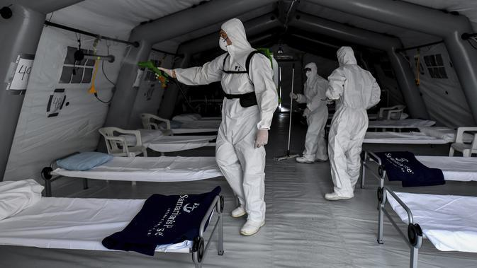 Petugas medis membersihkan rumah sakit lapangan darurat Samaritan's Purse di Cremona, Italia, Jumat, 20 Maret 2020. Rumah sakit lapangan ini dibangun untuk merawat pasien virus corona COVID-19 yang terus melonjak. (Claudio Furlan/LaPresse via AP)