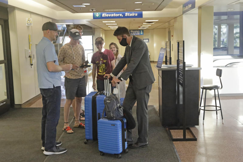 In this May 27, 2020, photo, Logan Morrison, 18, right, a missionary from The Church of Jesus Christ of Latter-day Saints, says goodbye to his family at Salt Lake City International Airport before leaving on his mission to St. Louis. After hastily bringing home 26,000 young men and women who were serving in foreign countries, the faith has begun sending many of them out again in their home countries with a new focus on online work that could stick even when the pandemic is over, church officials told The Associated Press. (AP Photo/Rick Bowmer)