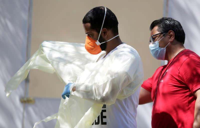 FILE PHOTO: Medical staff from Global Response Management prepare to take samples from a patient suspected of contracting coronavirus disease (COVID-19) at an isolation area of a hospital installed at a migrant encampment in Matamoros