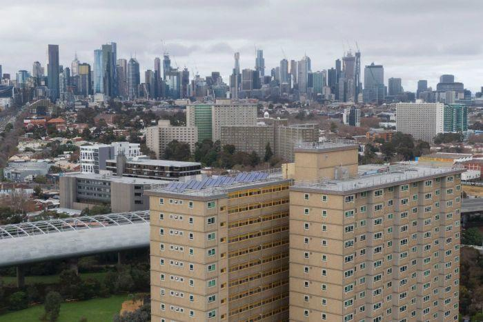 two public housing towers can be seen with the Melbourne city skyline in the background