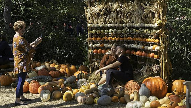 Seorang wanita mengabadikan foto di Desa Labu Dallas Arboretum, Texas, Amerika Serikat, 4 Oktober 2020. Desa Labu di Dallas Arboretum yang mendapat pengakuan nasional menghadirkan rumah-rumah labu dan berbagai objek kreatif dari 90.000 lebih labu, kundur, dan squash. (Xinhua/Dan Tian)