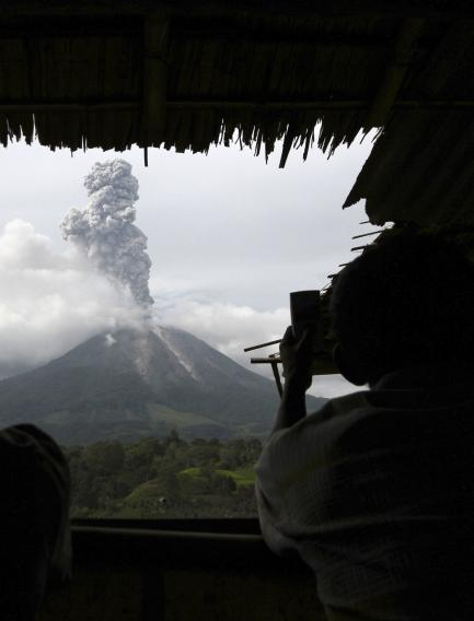 Villagers take pictures of Mount Sinabung erupting from a food stall at Simpang Empat village in Karo district