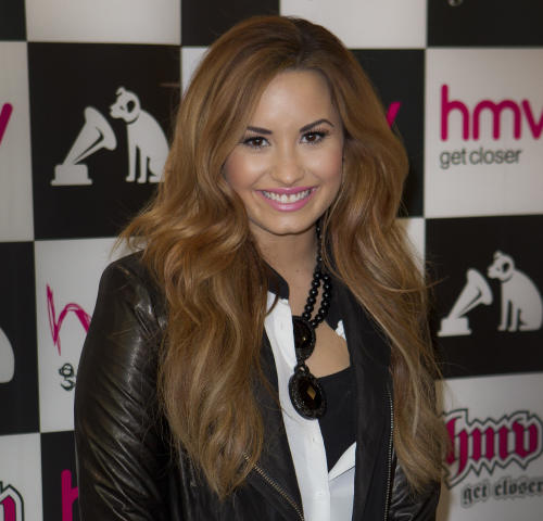 """FILE - In this April 3, 2012 file photo, U.S. singer Demi Lovato poses for photographs before she meets fans and signs copies of her new album, """"Unbroken,"""" at a central London music store. Pop star Lovato, also a new judge on """"The X Factor,"""" is set to host the 14th annual Teen Choice Awards, alongside """"Glee"""" co-star Kevin McHale, on Sunday, July 22, 2012. (AP Photo/Joel Ryan, File)"""