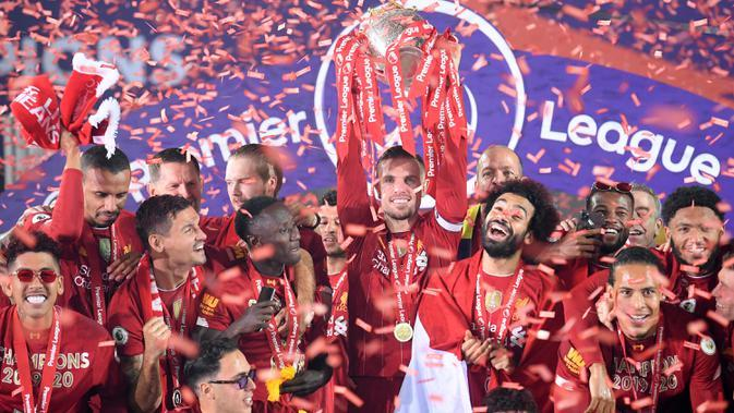 Gelandang Liverpool, Jordan Henderson, mengangkat trofi juara Premier league 2019-2020 di Stadion Anfield, Kamis (23/7/2020) dini hari WIB. Prosesi angkat trofi juara ini dilakukan usai pertandingan Liverpool melawan Chelsea. (AFP/Laurence Griffiths/pool)