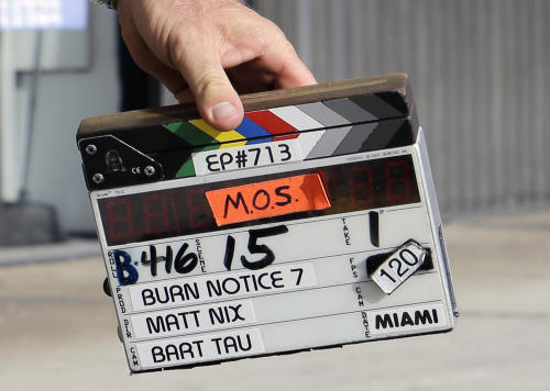 """This July 24, 2013, photo shows a clapperboard during taping for an episode of """"Burn Notice"""" in Miami. The cable spy drama is coming to an end after seven seasons with a big finale next Thursday, Sept. 12, 2013. (AP Photo/Alan Diaz)"""