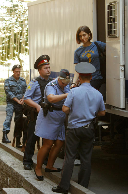 Nadezhda Tolokonnikova, top, a member of feminist punk group Pussy Riot is escorted to a court room in Moscow, Russia, Wednesday, Aug. 8, 2012. Prosecutors on Tuesday called for three-year prison sentences for feminist punk rockers who gave an impromptu performance in Moscow's main cathedral to call for an end to Vladimir Putin's rule, in a case that has caused international outrage and split Russian society.(AP Photo/Alexander Zemlianichenko)
