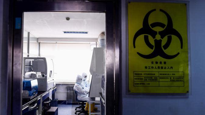 Petugas laboratorium melakukan pengujian sampel dari orang yang akan diuji untuk virus corona COVID-19 di sebuah laboratorium di Shenyang, provinsi Liaoning timur laut China, Rabu (12/2/2020). Pemimpin WHO di Jenewa mengganti nama virus corona Wuhan menjadi Covid-19. (STR/AFP)