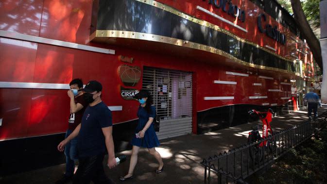 Pejalan kaki memakai masker di luar kasino tertutup di Mexico City (23/3/2020). Pemerintah kota mengumumkan langkah-langkah untuk menangani virus corona baru seperti menutup bar, disko, museum, kebun binatang, bioskop, teater dan pusat kebugaran COVID-19 mulai hari Senin. (AP Photo/Fernando Llano)
