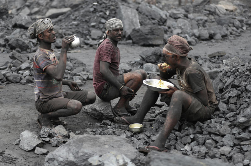 In this Oct. 23, 2019, photo, laborers eat lunch at a coal loading site in the village of Godhar in Jharia, a remote corner of eastern Jharkhand state, India. The fires started in coal pits in eastern India in 1916. More than a century later, they are still spewing flames and clouds of poisonous fumes into the air, forcing residents to brave sizzling temperatures, deadly sinkholes and toxic gases. (AP Photo/Aijaz Rahi)