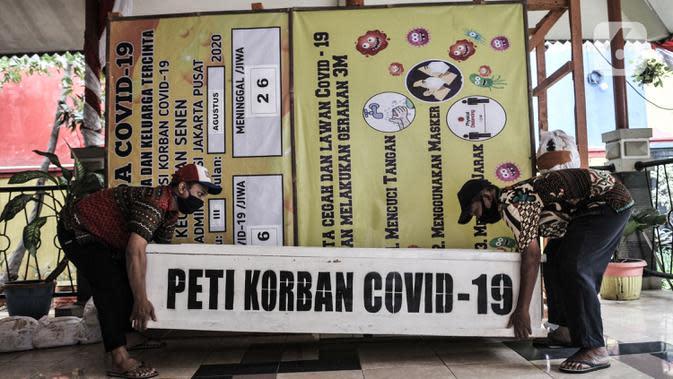 Pekerja mengangkat peti mati untuk dipajang di Kantor Kecamatan Senen, Jakarta, Kamis (13/8/2020). Pemkot Jakpus menyiapkan peti mati dan boneka pocong di setiap kecamatan sebagai peringatan akan bahaya Covid-19 dan imbauan untuk tidak mengabaikan protokol kesehatan. (merdeka.com/Iqbal Nugroho)