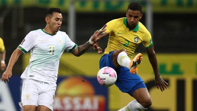 Bek Brasil, Danilo, berebut bola dengan pemain Bolivia pada laga kualifikasi Piala Dunia 2020 di Corinthians Arena, Sabtu (10/10/2020) pagi WIB. Brasil menang 5-0 atas Bolivia. (AFP/Buda Mendes/various sources)