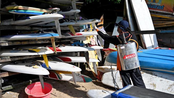Petugas kesehatan menyemprotkan disinfektan pada papan selancar di sepanjang pantai kawasan wisata Sanur, Bali, Senin (16/3/2020). Penyemprotan dilakukan sebagai salah satu langkah untuk mengantisipasi potensi penyebaran virus Corona COVID-19 di kawasan pariwisata tersebut. (SONNY TUMBELAKA/AFP)