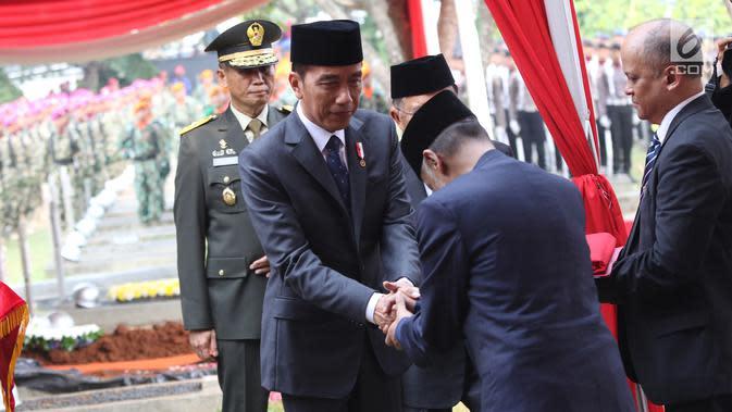 Presiden Joko Widodo bersalaman dengan kedua putra Presiden ke-3 RI Bacharuddin Jusuf Habibie usai meletakan karangan bunga di TMP Kalibata, Jakarta, Kamis (12/9/2019). (Liputan6.com/Herman Zakharia)
