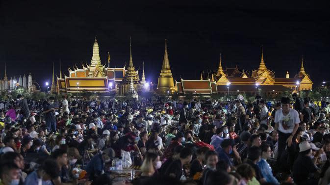 Demonstran pro-demokrasi menghadiri protes di Sanam Luang dengan The Grand Palace menyala di latar belakang di Bangkok, Thailand (19/9/2020). (AP Photo/Sakchai Lalit)