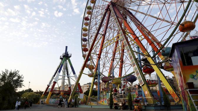 Warga terlihat di sebuah taman hiburan yang dibuka kembali di Istanbul, Turki, pada Senin (6/7/2020). Semua taman hiburan dan taman bermain di Turki pada Senin (6/7) dibuka kembali saat pemerintah melonggarkan lebih lanjut pembatasan terkait COVID-19. (Xinhua/Osman Orsal)