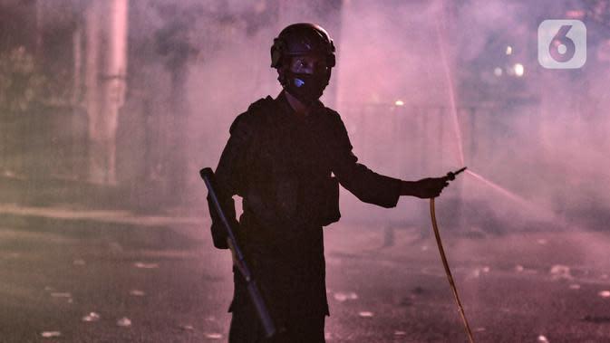 Seorang polisi saat berupaya membubarkan massa di kawasan Harmoni, Jakarta, Kamis (8/10/2020). Polisi berhasil membubarkan unjuk rasa ricuh yang dilakukan massa penolak UU Cipta Kerja dengan tembakan gas air mata dan watercanon. (merdeka.com/Iqbal S. Nugroho)