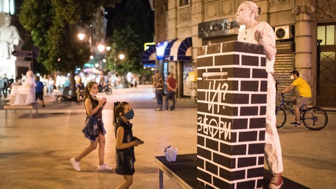 Seorang peserta berpakaian patung tampil dalam Statue Fest 2020 dengan tema