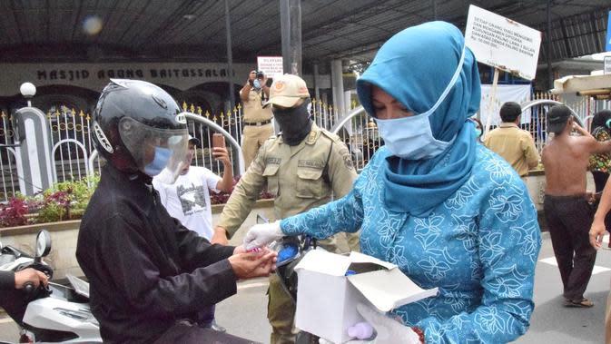 Bupati Banyumas, Achmad Husein dan Ketua Tim Penggerak PKK Banyumas membagikan hand sanitizer berbahan baku ciu dan masker gratis untuk masyarakat. (Foto: Liputan6.com/Humas Pemkab Banyumas/Muhamad Ridlo)