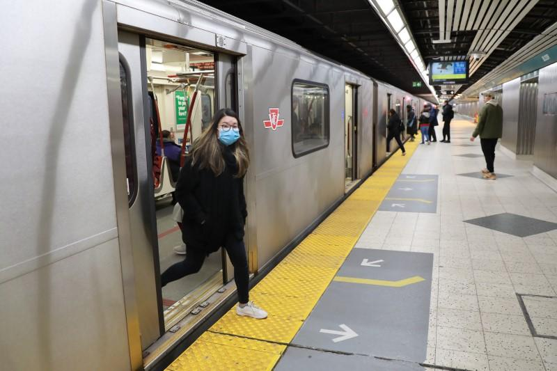 A woman wearing a mask, amid rising global numbers of novel coronavirus disease (COVID-19) cases, exits a subway train in Toronto